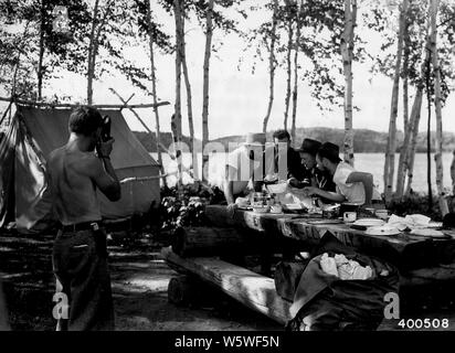 Photograph of Two Forest Officers; Scope and content:  Original caption: Two forest officers (Bill Trygg and Merle Moltrup) visit three vacationists camping at a canoe camp site on Birch Point on the south arm of Knife Lake. For a pictorial record of their trip one of the campers is taking a still picture of the forest officer. - Stock Photo