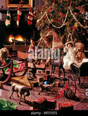 1970s 1980s OLD FASHIONED DECORATED CHRISTMAS TREE WITH POPCORN GARLANDS BY FIREPLACE ANTIQUE TOYS   - kx8773 PHT001 HARS MERRY PORCELAIN MODELS RECREATION TRADITION QUAINT DECEMBER CONCEPTUAL DECEMBER 25 STILL LIFE WARMTH ESTABLISHED GARLANDS ROCKING HORSE STYLISH COLLECTIBLES CREATIVITY JOYOUS PERIOD PINE TREE BABY CARRIAGE COLLECTIBLE FESTIVE OLD FASHIONED - Stock Photo