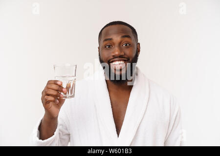 Thirsty young african man holding glass drinking water for body health isolated on white studio background - Stock Photo
