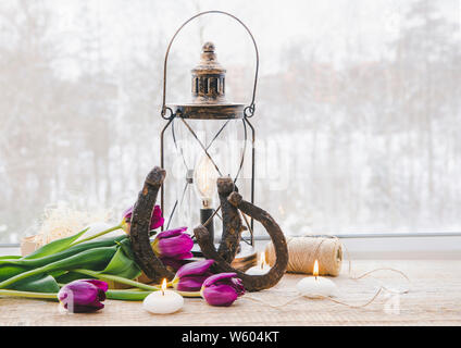 Old rusty horseshoes, brown vintage lantern with modern dimmable decorative light bulb switched on and white candles lit and  tulips on wooden window - Stock Photo