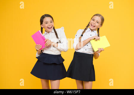 Study together. Knowledge day. School day. Girl with copy books or workbooks. Kids cute students. Schoolgirls best friends excellent pupils. School friendship. Schoolgirls wear school uniform. - Stock Photo