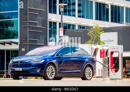 Adelaide CBD, Australia - November 18, 2017: Tesla Model X car and Tesla Supercharger EV charging station in city centre on Franklin Street on a day - Stock Photo