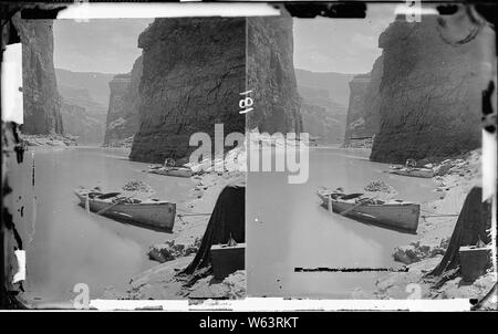 Colorado River. Marble Canyon, 1872. Shows two boats anchored, one with Major Powell's chair with the two life preservers on either arm. Also in the foreground is the photo tent and box with a funnel on top of it. Old nos. 448, 475, 890. - Stock Photo