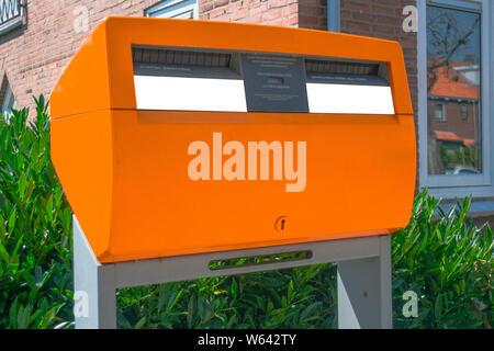 Posting a letter in the Netherlands - Orange Dutch letterbox - Stock Photo