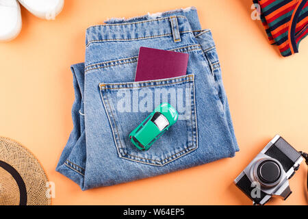 Travel symbol items flat lay with white sneakers, passport in the pocket of comfortable jeans, toy car and photo camera on orange background. Frame co - Stock Photo