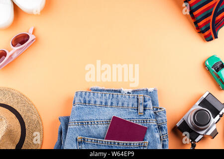 Travel symbol items flat lay with white sneakers, passport, pink sunglasses, comfortable jeans, toy car and photo camera on orange background. Frame c - Stock Photo