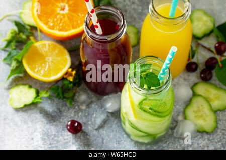 Various refreshments drinks - detox cucumber water, cherry juice and orange juice on stone table. - Stock Photo