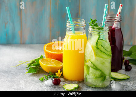 Various refreshments drinks - detox cucumber water, cherry juice and orange juice on stone table. Copy space for your text. - Stock Photo