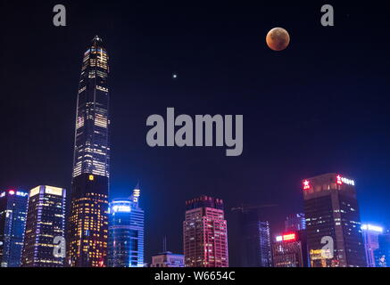 View of the longest 'blood moon' eclipse of this century, right, which passes into the Earth's shadow, and the Mars in the sky over skyscrapers during - Stock Photo