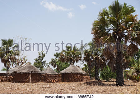 Simple settlement of mud huts in the northern Togo in western Africa - Stock Photo