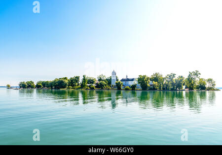 Fraueninsel, Frauenchiemsee on lake Chiemsee in the  morning sunrise with boat, Sailboat, church, monastery. Bavaria, Bayern, Germany - Stock Photo