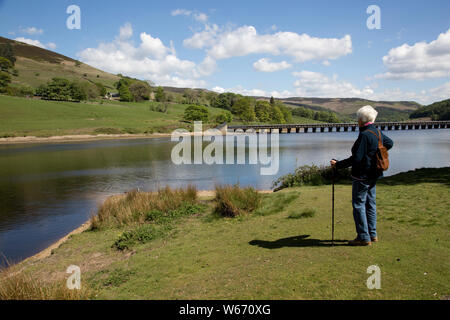 Woman walker enjoying view of Ladybower Reservoir, the largest (holding 6300 million gallons) of three water storage reservoirs in the Derwent Valley, - Stock Photo