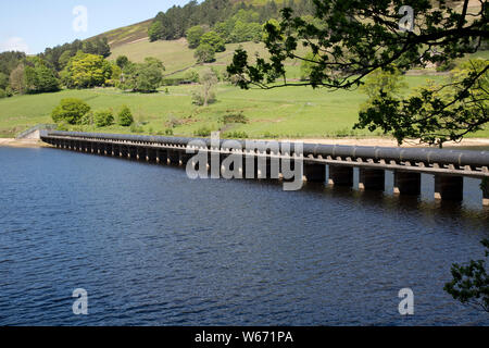 Twin pipe aqueducts at Ladybower Reservoir, the largest (holding 6300 million gallons) of three water storage reservoirs in the Derwent Valley, Peak D - Stock Photo