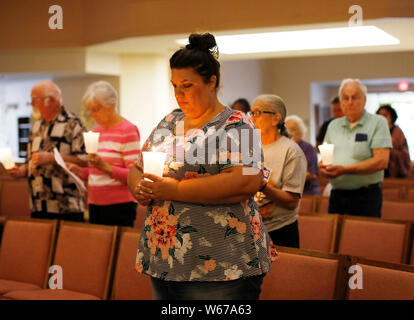 San Francisco, California, USA. 30th July, 2019. People hold candles as they mourn for the victims of a garlic festival shooting incident in San Jose, California, the United States, July 30, 2019. A six-year-old boy and a 13-year-old girl were among the three victims killed in a shooting at an annual garlic festival held in Gilroy city, Northern California, Gilroy Police Chief Scot Smithee said Monday. The police chief also updated the number of total injuries to 12 who survived the shooting at the annual Gilroy Garlic Festival. The injuries were previously put at 15 on Sunday. Credit: Xinhua/ - Stock Photo