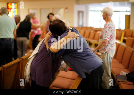 San Francisco, California, USA. 30th July, 2019. People hug each other as they mourn for the victims of a garlic festival shooting incident in San Jose, California, the United States, July 30, 2019. A six-year-old boy and a 13-year-old girl were among the three victims killed in a shooting at an annual garlic festival held in Gilroy city, Northern California, Gilroy Police Chief Scot Smithee said Monday. The police chief also updated the number of total injuries to 12 who survived the shooting at the annual Gilroy Garlic Festival. The injuries were previously put at 15 on Sunday. Credit: Xinhu - Stock Photo