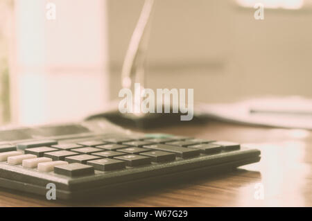 Close up of a calculator placed on office desk. A loan application form at a distance. Business Finance Concept. Vintage background. Isolated. Copy sp - Stock Photo