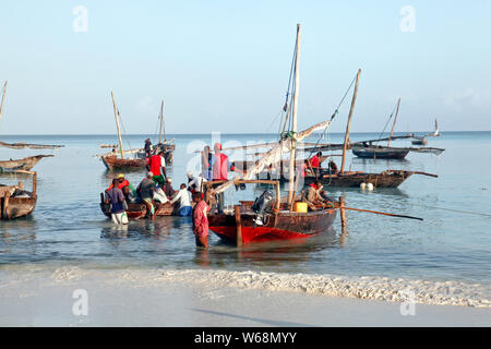 Beaches of Zanzibar in Tanzania, Africa with fishing boats and tourism - Stock Photo