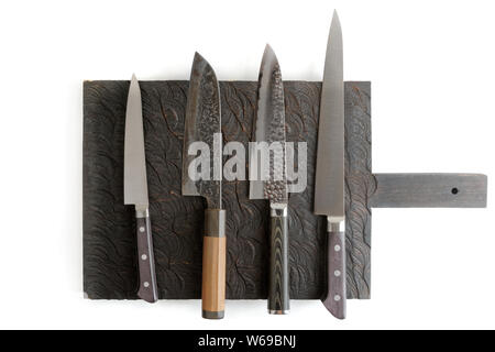 Four different knives on black cutting board, isolated on white with shadows - Stock Photo