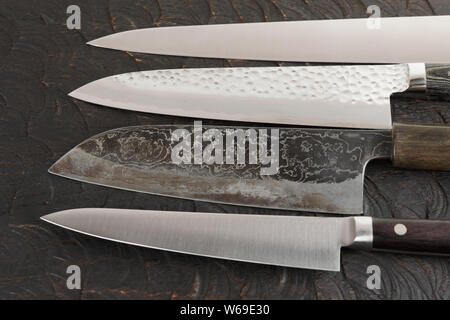 Four new and used knives on black cutting board - Stock Photo