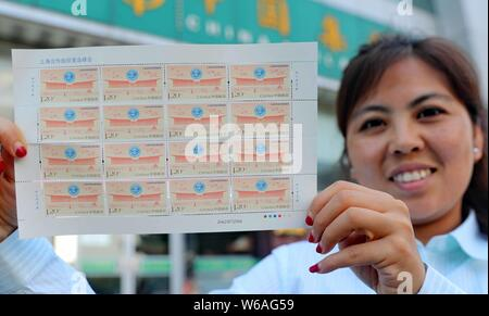 A Chinese employee shows a sheet of stamps commemorating the 18th Shanghai Cooperation Organization (SCO) summit at a China Post Office in Qinhuangdao - Stock Photo
