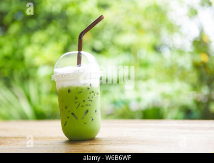 iced green tea in plastic cup / matcha green tea latte frappe and straw on wooden table with nature background - Stock Photo