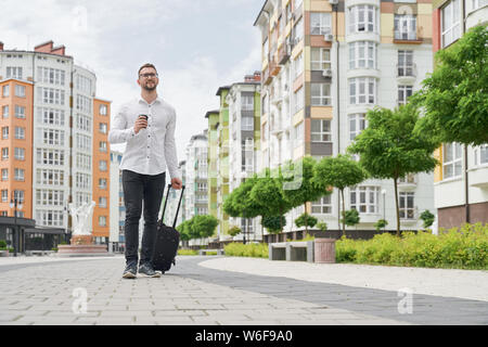 Handsome bearded student in glasses with coffee cup walking down street, looking at building. Young man wearing in white shirt with suitcase on background of multistory houses. - Stock Photo
