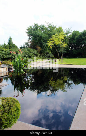 A large man made pond reflecting the sky and trees in the Serenity Garden at Olbrich Botanical Gardens in Madison, Wisconsin, USA - Stock Photo
