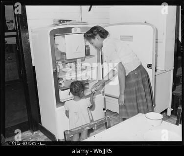 Mrs. James Robert Howard gives her daughter a banana from electrical refrigerator. The Howard bill for electricity is about $4 monthly; they are on a meter and pay bills directly to Appalachian Power Company. Gilliam Coal and Coke Company, Gilliam Mine, Gilliam, McDowell County, West Virginia. - Stock Photo