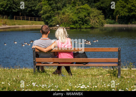 Loving couple cuddling on park-bench, overlook a park lake looking at the wildlife. - Stock Photo