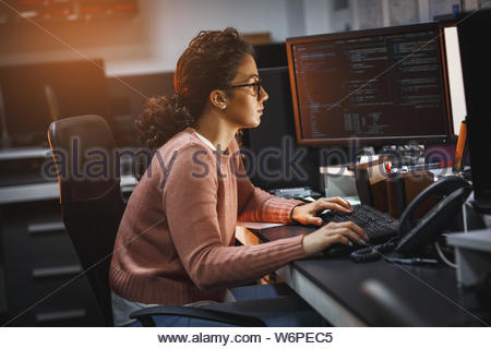 Female programmer working on new project.She working late at night in her office. - Stock Photo