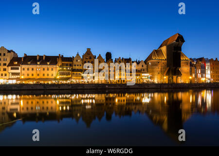Scenic view of the lit Crane and other old buildings along the Long Bridge waterfront at the Main Town in Gdansk, Poland, in the evening. - Stock Photo
