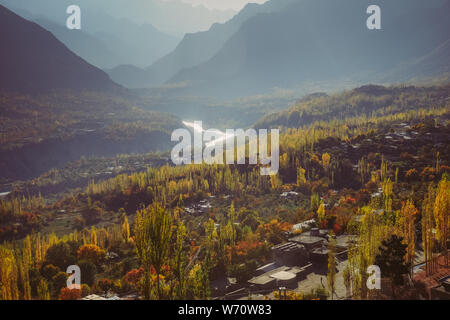 Colorful foliage in autumn. Nature background of forest and river against Karakoram mountain range in Hunza Nagar Valley. Gilgit Baltistan, Pakistan. - Stock Photo