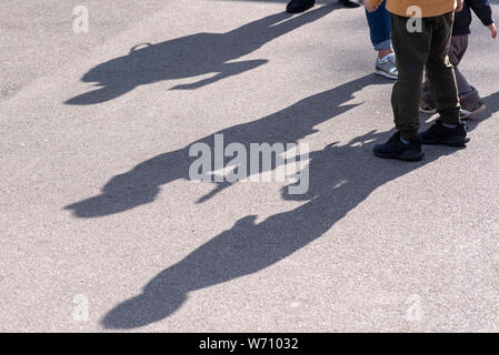 Shadows and Silhouettes of three Children playing in a Street on surface of asphalt Road as Background or Texture - Stock Photo