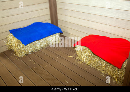 bales of hay on floor near wooden walls - Stock Photo