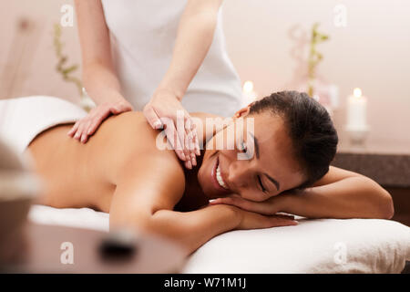 Portrait of beautiful woman smiling happily while enjoying massage in luxury spa, copy space - Stock Photo