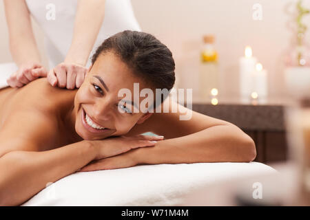 Portrait of beautiful young woman smiling at camera while enjoying massage in spa, copy space - Stock Photo