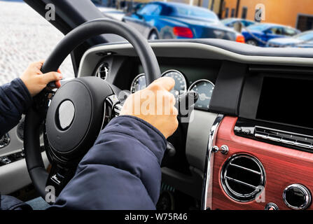 Male hands holding car steering wheel. Hands on steering wheel of a car driving. Young Man driving a car inside cabin. Multimedia system. Man Travelin - Stock Photo