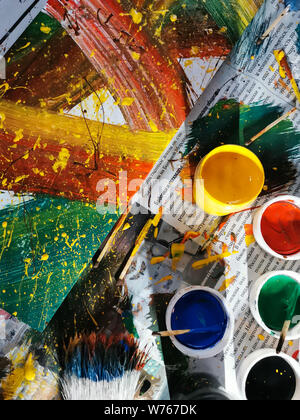 colorful bright colors, brushes and abstract painting on newspaper background. cans of different colors and contemporary art - Stock Photo