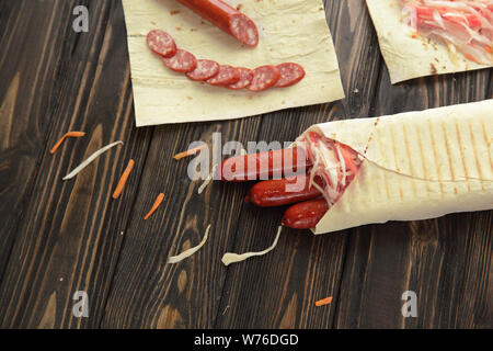 sausage in pita bread on wooden background.photo with copy space - Stock Photo