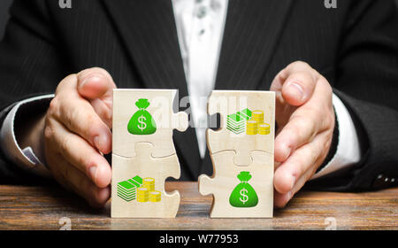 Businessman combines money puzzles. Fundraising, attracting investments for the implementation of business projects and startups. Crowdfunding. Accumu - Stock Photo