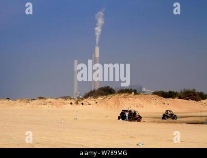 Dune buggies on Zikim Beach on Mediterranean coast in Israel sit in front of the Rutenberg Power Plant smoke stacks. - Stock Photo