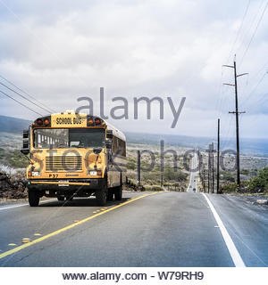 Hawaii, United States - September 07, 2012 : A yellow schoolbus driving on a long straight road around the big island of Hawaii - Stock Photo