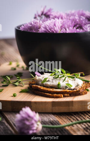 A delicious garlic and chive cream cheese spread on herbed crackers next to a bowl of purple chive flowers. - Stock Photo