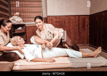 Woman closing her eyes relaxing during her massage. - Stock Photo