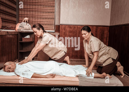 Woman relaxing during her four-hand massage session. - Stock Photo