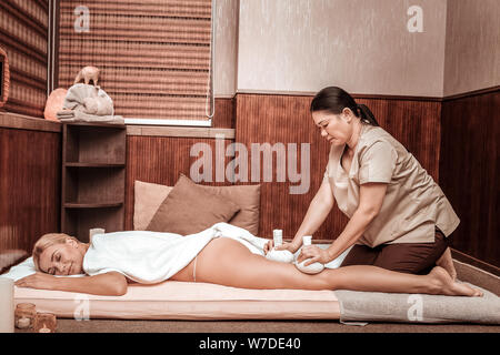 Woman relaxing during her hip massage with bags. - Stock Photo