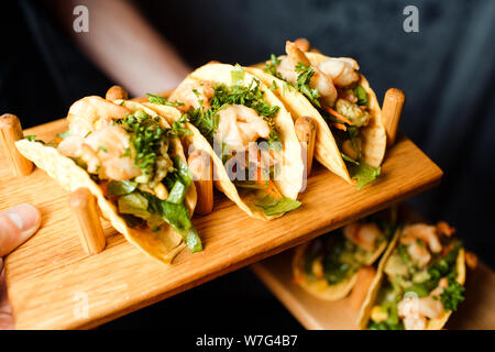 Shrimp appetizers with vegetables and herbs on a wooden plate in a beer bar. - Stock Photo