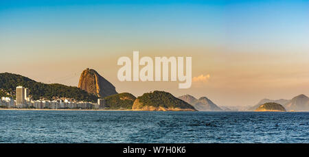 Panoramic image of Copacabana beach and Sugar Loaf in the background during late afternoon in Rio de Janeiro - Stock Photo