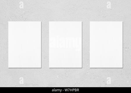 Three empty white vertical rectangle poster mockups with soft shadows on neutral light grey concrete wall background. Flat lay, top view - Stock Photo
