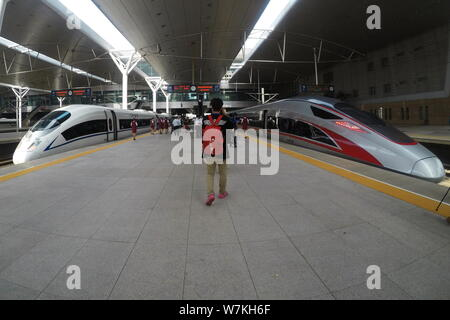 A 'Fuxing' high-speed bullet train on the Beijing-Tianjin Intercity Railway, right, and a CRH (China Railway High-speed) bullet train are pictured at - Stock Photo